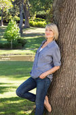 Woman leaning on tree trunk in park — Stock Photo