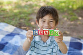 Happy boy holding block alphabets as 'learn' at park — Stock Photo