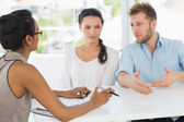 Therapist speaking with couple sitting at desk — Stock Photo