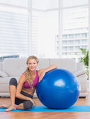 Slim blonde sitting beside exercise ball — Stock Photo