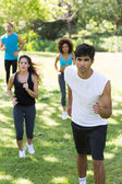 Athletes jogging on grassy land  — Stock Photo
