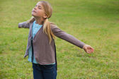 Girl with arms outstretched at park — Stockfoto