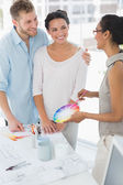 Interior designer showing colour wheel to happy clients — Stock Photo