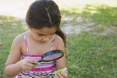 Girl examining a leaf with magnifying glass at park — Foto Stock