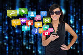 Glamorous brunette using smartphone with app icons — Stock Photo