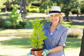 Woman holding potted plant in garden — Stock Photo