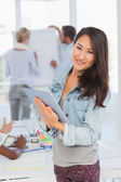Asian woman using her tablet while her colleagues are working — Stock Photo