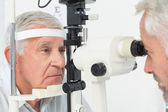 Optometrist doing sight testing for senior patient — Photo