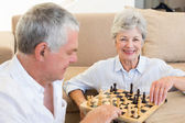 Senior couple sitting on floor playing chess — Stock Photo