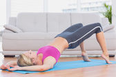Blonde lifting her pelvis on exercise mat — Stock Photo