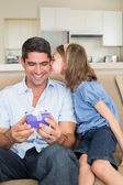 Girl kissing father holding gift — Stock Photo