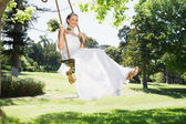 Bride swinging in garden — Stock Photo