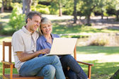 Couple using laptop on park bench — Stock Photo