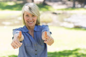 Woman gesturing thumbs up in park — Stock Photo