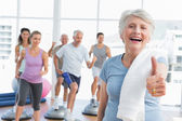Senior woman gesturing thumbs up with people exercising — Stock Photo