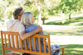 Couple sitting on park bench — Stock Photo