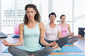 Women in lotus pose with eyes closed at fitness studio — Stock Photo