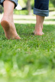 Woman walking on grassy land — Stock Photo