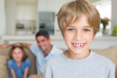 Boy with family in background — Stock Photo