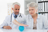 Male doctor with senior patient using stress buster ball — Stock Photo
