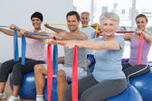 Class holding out exercise belts while sitting on fitness balls — Stock Photo