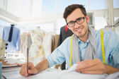 Smiling male fashion designer working on his designs — Stock Photo
