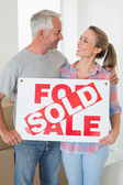 Happy couple standing and holding sold sign — Stock Photo