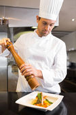 Concentrated male cook grinding pepper on food in kitchen — Stock Photo