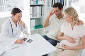 Expectant couple and doctor discussing over reports — Stock Photo