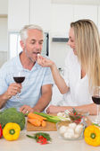 Affectionate couple preparing dinner together and drinking red wine — Stock Photo