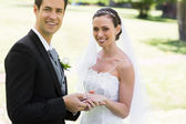 Groom placing ring on brides finger at park — Stock Photo