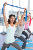 Class holding up exercise belts at yoga class — Stock Photo