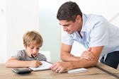 Son doing homework with father — Stock Photo