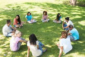 Friends sitting in a circle at park — Stock Photo
