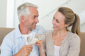 Happy couple sitting on couch toasting with white wine — Stock Photo