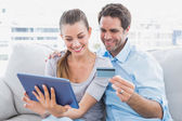 Happy couple relaxing on the couch shopping online with tablet pc — Stock Photo