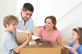Family unpacking cardboard box — Stock Photo