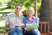 Couple with books sitting on bench — Stock Photo