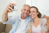 幸せなカップルはソファの上、selfie を一緒に撮影 — ストック写真