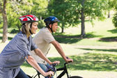Happy couple cycling in park — Stock Photo