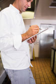 Cook writing on clipboard in kitchen — Stock Photo