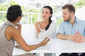 Therapist talking with couple sitting at desk — Stock Photo