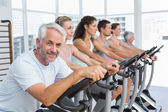 People working out at spinning class in gym — Stock Photo