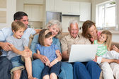 Family using laptop in living room — Stock Photo