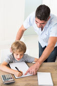 Father assisting boy in solving maths — Stock Photo