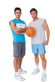 Two fit young men with scales and basketball — Stock Photo