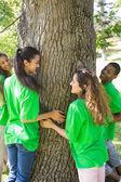 Environmentalists standing around tree trunk — Stock Photo