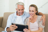 Happy couple using tablet pc together on the couch — Stock Photo