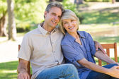 Affectionate couple sitting on bench — Stock Photo