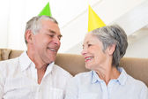 Senior couple sitting on couch wearing party hats — Stock Photo